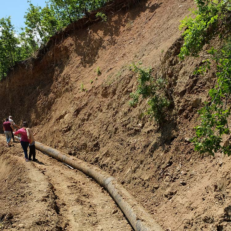 A water pipe lying beneath a very steep dirt hill.