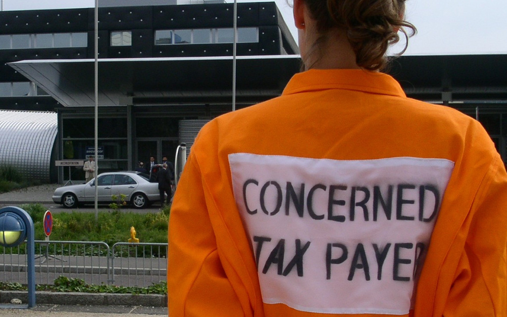 """A person in a workers overall seen from behind with the words """"concerned tax payer"""" printed on the back."""